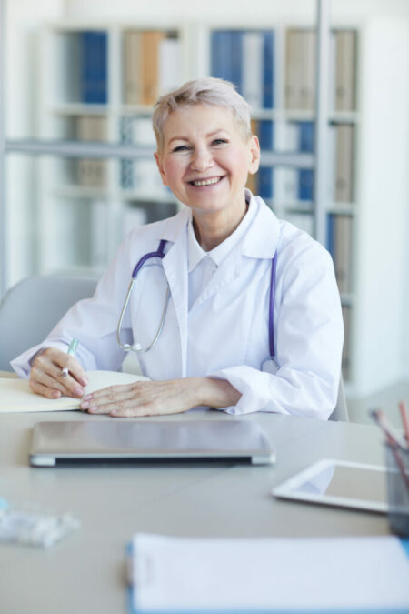 Mature Female Doctor Posing at Desk in Office
